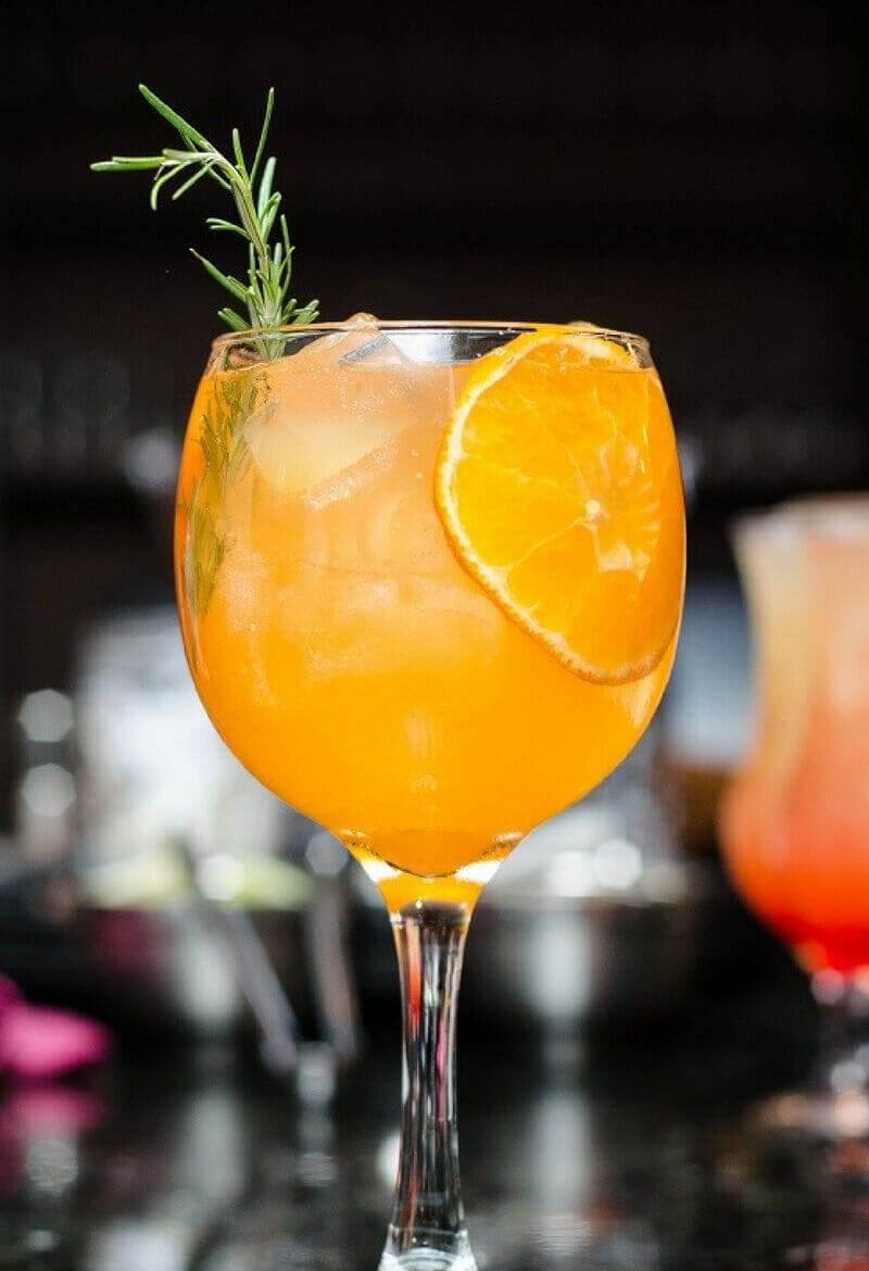 Orange Mango Mimosa on a bar garnished with an orange slice and rosemary sprig.