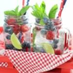 Two raspberry and blueberry silver tequila mojitos sitting on a red gingham napkin in a red tray with patriotic drinking straws.