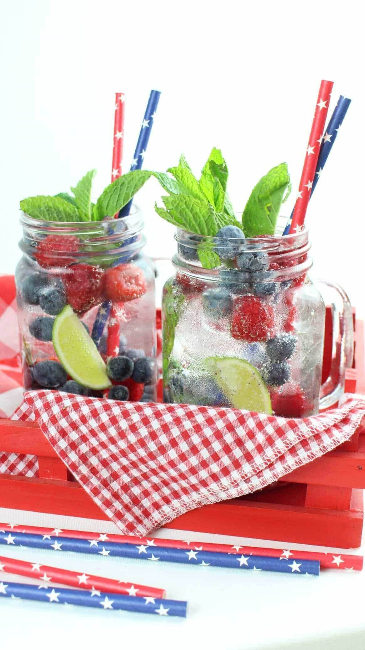 Two raspberry and blueberry mojitos on a red gingham napkin in a red tray with patriotic drinking straws.