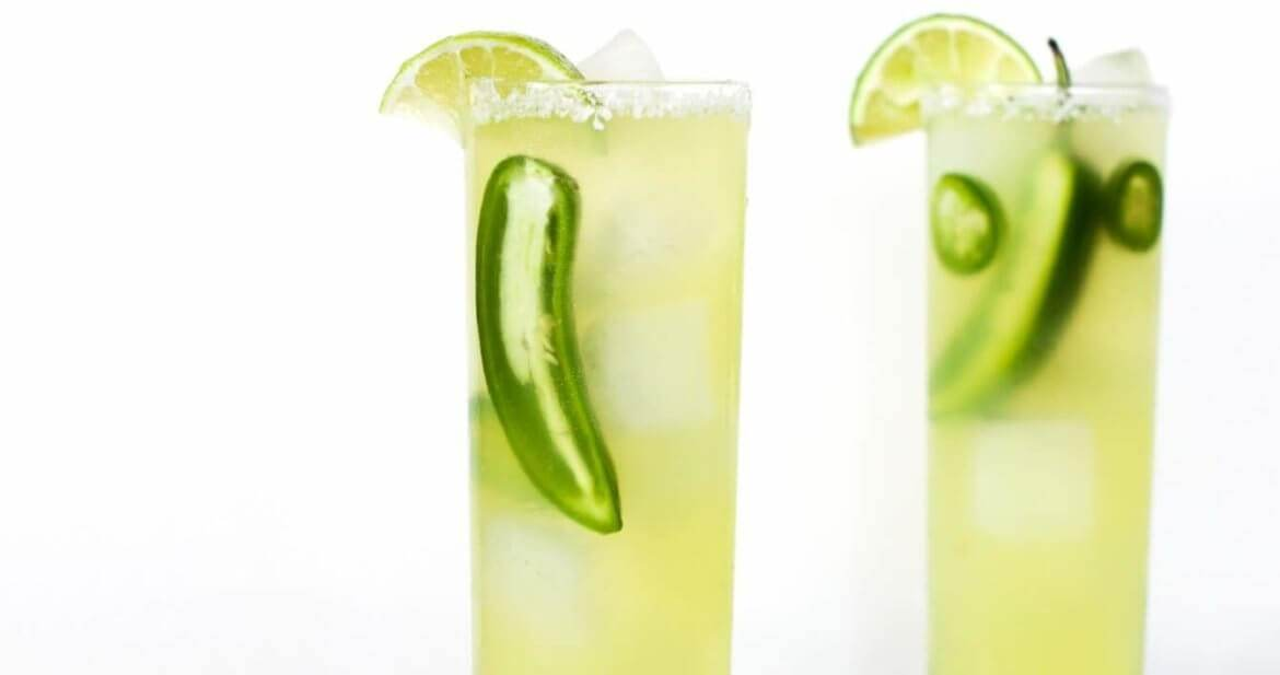 Two sparkling spicy margaritas with fresh jalapeno slices and lime on a marble serving tray on a table dressed with a blue and white cloth.