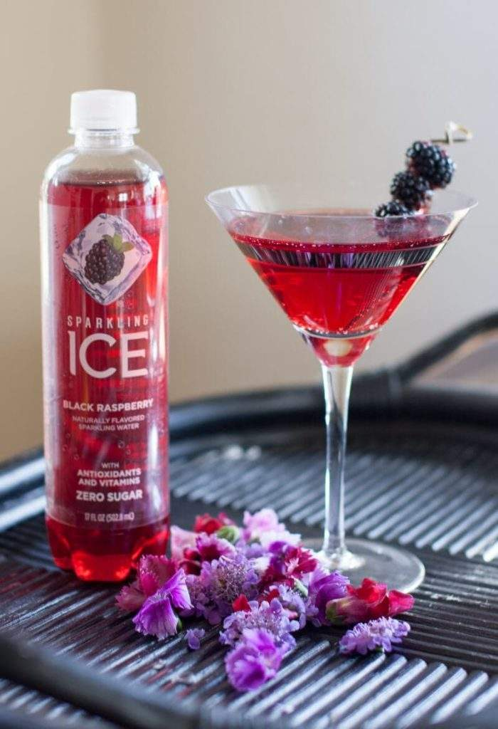 Cocktail Recipe Black Raspberry Vodka Martini made with Sparkling Ice. Served on a bamboo tray and garnished with blackberries on a cocktail pick.