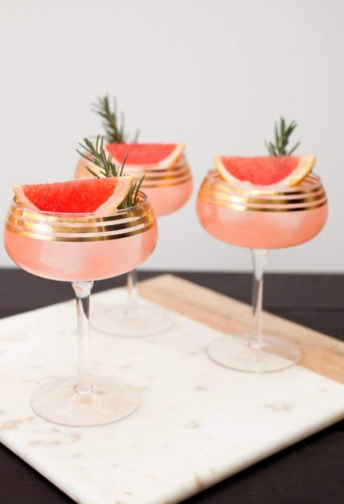 Elderflower Grapefruit Sparkler Cocktail Recipe served in a gold-rimmed coupe on a marble tray. Garnished with rosemary sprig and grapefruit wedge.