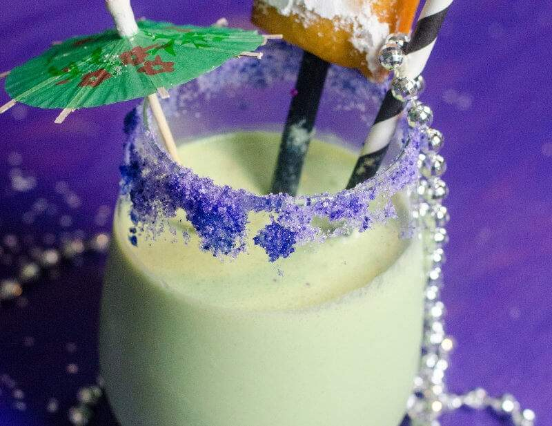 Mardi Gras King Cake Shake recipe garnished with a beignet and cocktail umbrella and strewn with mardi gras beads on a purple background.
