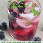 Cocktail made with fresh blackberries served in a glass, garnished with a sprig of fresh thyme.