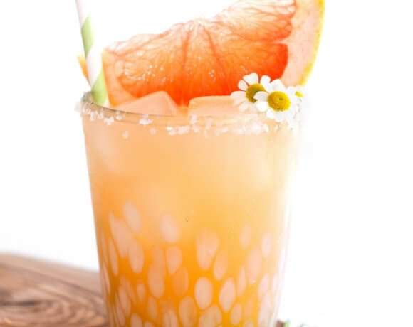 Sparkling Paloma Tequila Cocktail served in a clear glass with white spots. The drink is garnished with miniature daisies and a slice of grapefruit with a paper straw.
