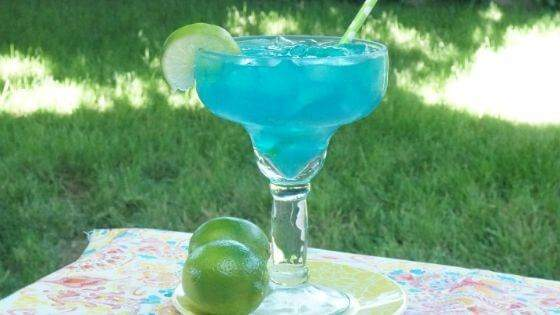 An electric blue margarita on a pastel table cloth with two limes