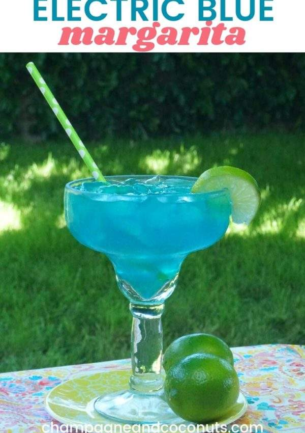 An electric blue margarita garnished with a lime wheel with a green straw on a table in a backyard