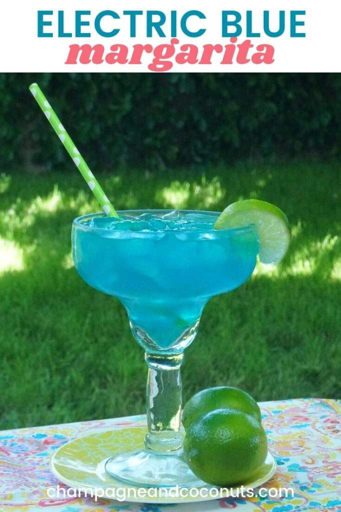 A blue cocktail garnished with a lime wheel with a green straw on a table in a backyard. Text: Electric Blue Margarita
