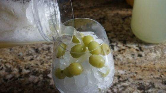 Pour the drink over the ice and frozen grapes