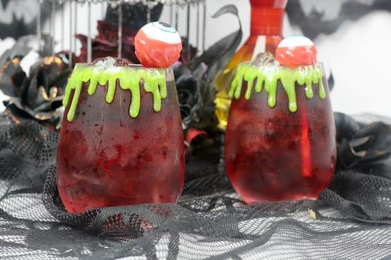 two Halloween cocktails garnished with eyeball cocktail pics