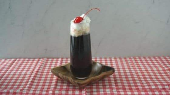 A cocktail topped with whipped cream and a cherry on a wood plate on a red and white gingham tablecloth.